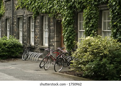 Three bicycles parked at Trinity College in Dublin in front of an ivy-covered building.