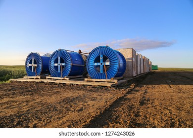 Three big blue cable drums and cable spools and wooden boxes standing on the wooden cradles at the storage dirt pad in tundra in summer