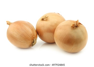 three big brown onions on a white background