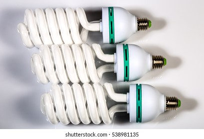 Three Big powerful modern energy saving fluorescent lamp. Macro shot. White background, shadows.