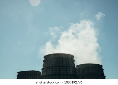 Three big tower of CHPP close-up. White steam from wide pipe of CHP on blue sky. Industrial background image of TPP with copy space. Huge pipes of thermal power plant produce steam for electric power.