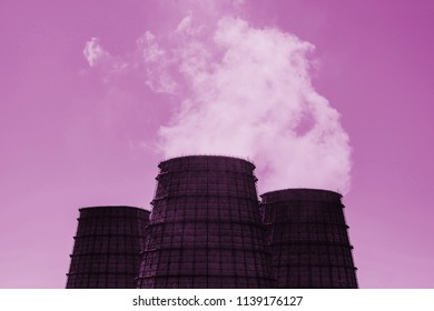 Three big tower of CHPP close-up. Steam from wide pipe of CHP on sky. Industrial background of TPP in pink tones with copy space. Huge pipes of thermal power plant produce steam for electric power.