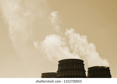 Three big tower of CHPP close-up. Steam from wide pipe of CHP on sky. Industrial background of TPP in sepia tones with copy space. Huge pipes of thermal power plant produce steam for electric power.