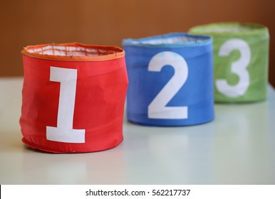 three bigjars for toys with numbers one two three and the number one in focus