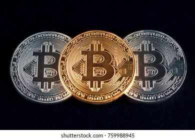 Three bitcoins golden and silver glowing on black background closeup