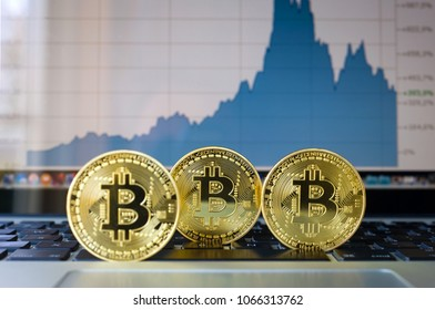 Three bitcoins on a laptop with price trend graffic on the background