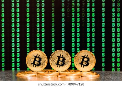 three bitcoins with sequence of green numbers in background