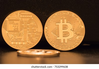 Three Bitcoins, two standing and showing both sides of the coins