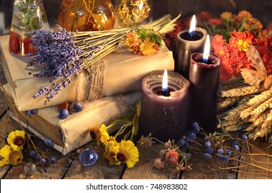 Three black candles, lavender bunch, healing herbs and flowers on planks. Occult, esoteric, divination and wicca concept. Alternative medicine and homeopathic vintage background