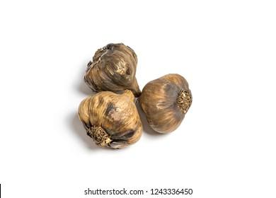 Three black garlics isolated on white.