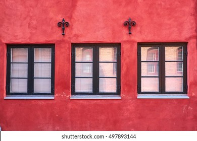Three black painted colonial style windows of wood, fastened in a red plastered facade, with two iron wall anchors, of a townhouse in Elsinore, Denmark