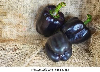three black paprika's on a piece of jute.