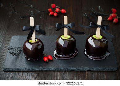 Three black poison caramel apples. Traditional dessert recipe for Halloween party. Selective focus.