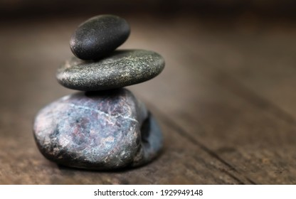 Three black stones stacked on a wooden base, zen