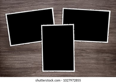 three blackened old vintage photo templates on rustic wooden background
