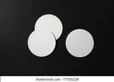 Three blank beer coasters on black paper background. Flat lay.