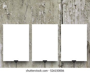 Three blank frames hanged by clips against gray weathered wood background