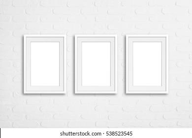 Three  blank frames on white bricks textured wallpaper, mock up