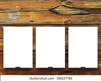 Three blank frames supported by clips against weathered brown wooden background