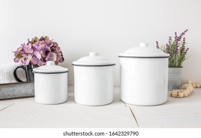 Three blank round kitchen containers on white background with plant decor, rustic canister label mockup