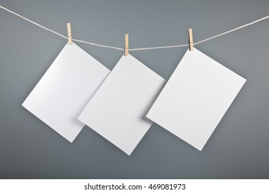 Three blank sheets pinned to a string with a grey wall in the background.