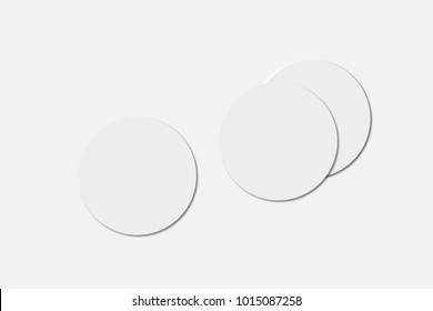 Three blank white beer coasters on paper