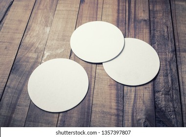Three blank white beer coasters on wooden background. Responsive design mockup.