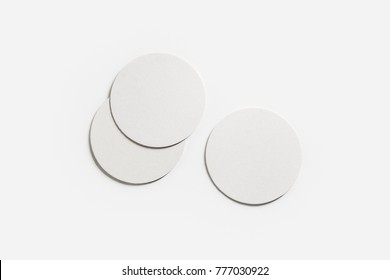 Three blank white beer coasters on paper background. Responsive design mockup. Flat lay.