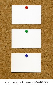 Three blank white business cards attached to a cork notice board.
