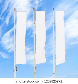Three blank white flags on flagpoles against cloudy blue sky, corporate flag mockup to ad logo, text or symbol, company identity flag template with copy space