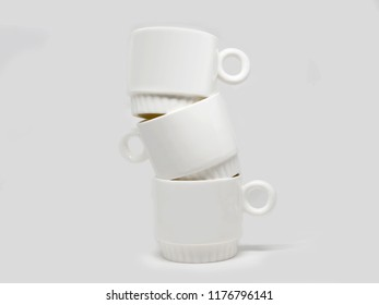 Three blank white mugs standing over each other isolated on a white background
