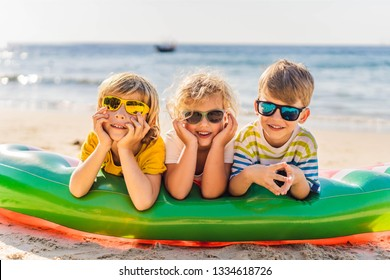 Three blond kids in sunglasses are lying on the beach