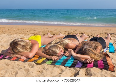 Three blonde girls sunbathing together on beach with sea