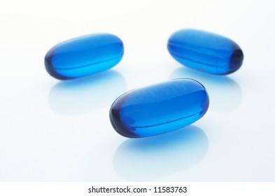 Three blue capsules on white background