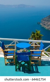 Three blue chairs and a small table on beautiful terrace in Santorini with Caldera view and Aegean sea. As always clear blue sky in hot Greece. Great atmosphere for vacation and holidays.