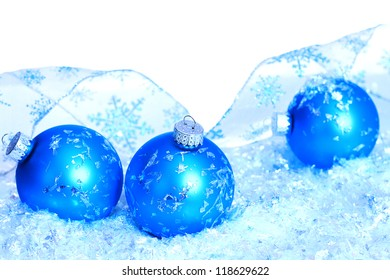 Three blue Christmas ball ornaments in faux snow with blue reflection alongside of them sparkly ribbon curled
