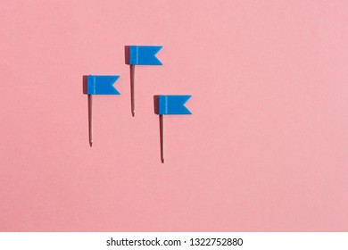 Three blue little flag pins on a pink background. View from above