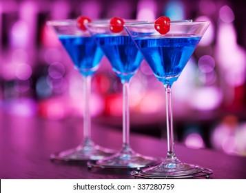 Three Blue Martini cocktails on a bar