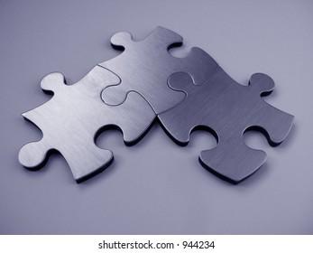 Three blue metallic jigsaw pieces