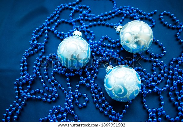 Three blue New Year's balls and blue beads on a dark background. Christmas decorations