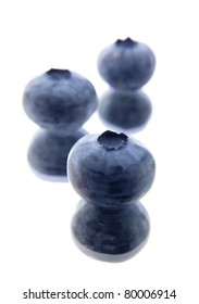 three blueberries on a mirror