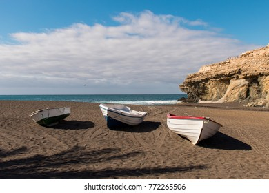 Three boats in Ajuy Fuerteventura Black Sand beach with caves and palm tree shaped shade