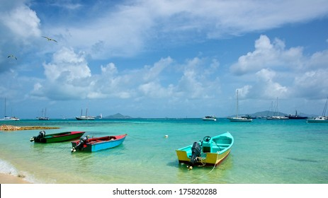 Three boats float anchored to the beach on a Caribbean Shore.