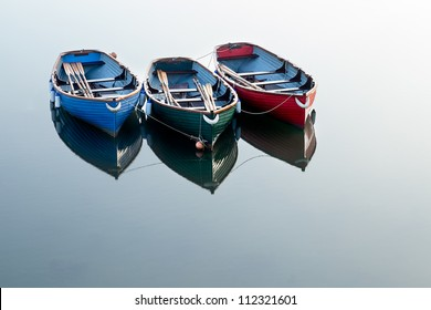 Three boats on clear water with the only reflections coming from the boats.  Each boat is painted a different colour: Red, Green & Blue.
