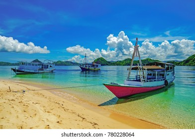 Three boats on the shore of a tropical island with clear water and a sandy beach