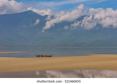 Three boats in pond near little sand island. Mountains, blue sky, white clouds reflected in transparent water