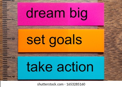 Three bookmark stickers with the words dream big, set goals, take action on a dark natural wooden table