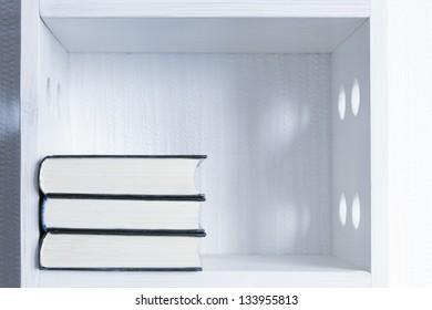 three books laying on the white shelf