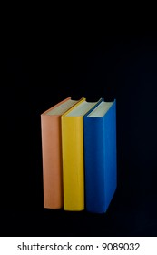 Three books,with orange, yellow and blue spines, lined up in a row. Isolated against black background.