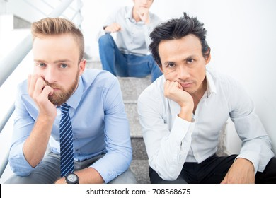 Three Bored Business Men Sitting on Stairs